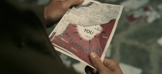 "Screenshot from ""Dunkirk"" showing soldier holding leaflet saying ""we surround you"""